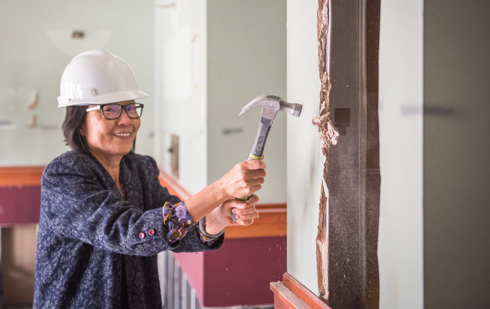 Yeh takes a ceremonial swing at the wall inside Hale Library's southeast entrance. Photo courtesy of Kansas State.