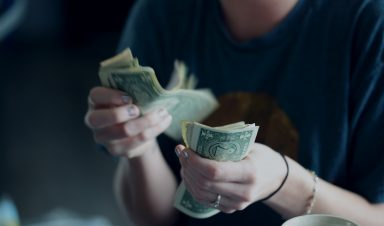 Woman's hands counting dollar bills